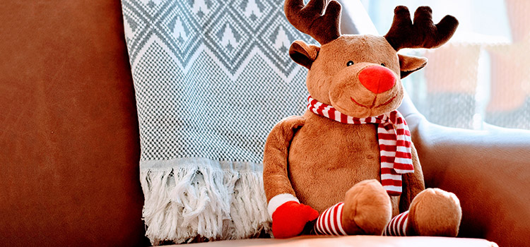 A reindeer plushie sitting on a couch